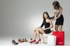 Duas mulheres glamoroso que tentam os saltos elevados fotografia de stock