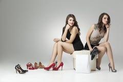 Duas mulheres glamoroso que tentam os saltos elevados Foto de Stock Royalty Free
