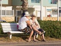 Duas mulheres idosas que sentam-se em um banco e em uma conversa no passeio Foto de Stock Royalty Free