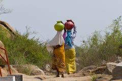 Duas mulheres indianas levam a água em suas cabeças dentro Fotografia de Stock