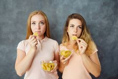 Duas mulheres indiferentes que comem microplaquetas de batata foto de stock royalty free