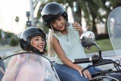 Duas mulheres louras da irmã feliz na bicicleta do side-car imagem de stock