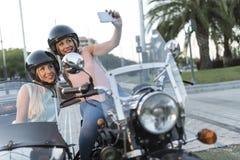 Duas mulheres louras da irmã feliz na bicicleta do side-car fotografia de stock royalty free