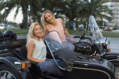 Duas mulheres louras da irmã feliz no side-car foto de stock royalty free