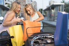 Duas mulheres louras da irmã feliz no side-car que olha sacos de compras foto de stock