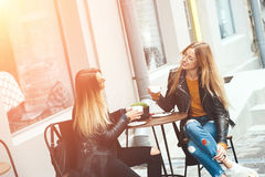 Duas mulheres louras novas bonitas que bebem o café e que bisbilhotam no restaurante agradável exterior Fotos de Stock