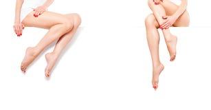 Duas mulheres magros bonitas com o tratamento de mãos vermelho, sentando-se na bandeira Fotografia de Stock