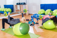 Duas mulheres magros que exercitam com barbell e bola do suíço na frente do espelho no salão do treinamento Imagens de Stock Royalty Free