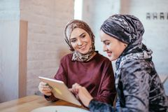 Duas mulheres muçulmanas no café, compram em linha usando a tabuleta eletrônica imagens de stock