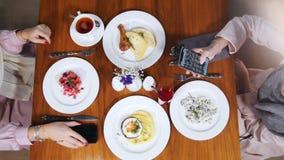 Duas mulheres muçulmanas que sentam-se em um restaurante Placas com um alimento vídeos de arquivo