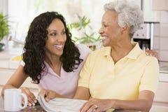 Duas mulheres na cozinha com jornal e café Foto de Stock Royalty Free
