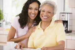 Duas mulheres na cozinha com jornal e café Fotos de Stock Royalty Free
