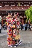 Duas mulheres na roupa japonesa tradicional abraçam-se maciamente no templo de Senso-ji no Tóquio, Japão imagem de stock