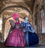 Duas mulheres nas máscaras e nos trajes azuis e cor-de-rosa ornamentado que estão sob os arcos no mercado de Railto, Veneza duran Imagens de Stock