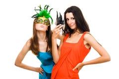 Duas mulheres nas máscaras e nos vestidos da cor que flertam Fotografia de Stock Royalty Free