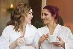 Duas mulheres nas vestes brancas que bebem o ch? ap?s tratamentos dos termas foto de stock royalty free