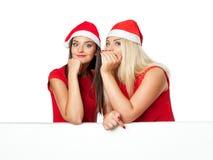 Duas mulheres no chapéu do ajudante de Santa com placa branca vazia Fotografia de Stock