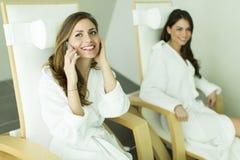 Duas mulheres nos roupões que relaxam nos termas Imagens de Stock