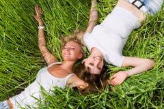 Duas mulheres novas colocam na grama verde ao ar livre foto de stock