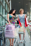 Duas mulheres novas com carros de compra. Fotos de Stock Royalty Free
