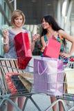 Duas mulheres novas com carros de compra. Imagem de Stock Royalty Free