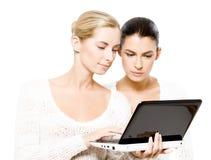 Duas mulheres novas com netbook Fotografia de Stock Royalty Free