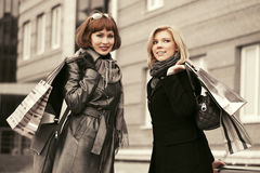Duas mulheres novas da forma com sacos de compras que andam na rua da cidade fotografia de stock