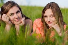 Duas mulheres novas de sorriso felizes bonitas na grama Fotos de Stock