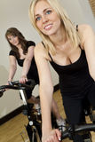 Duas mulheres novas em bicicletas de exercício na ginástica Fotografia de Stock Royalty Free