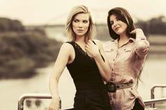 Duas mulheres novas felizes da forma na rua da cidade Foto de Stock Royalty Free