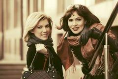 Duas mulheres novas felizes da forma na rua da cidade fotografia de stock