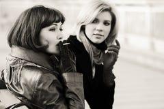 Duas mulheres novas felizes da forma que fumam um cigarro Fotografia de Stock