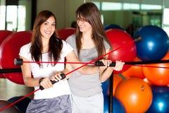 Duas mulheres novas felizes na ginástica imagens de stock