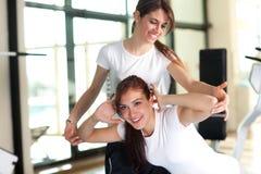 Duas mulheres novas felizes na ginástica fotos de stock royalty free
