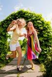 Duas mulheres novas felizes runing em um parque imagens de stock