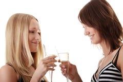 Duas mulheres novas ocasionais que apreciam o champanhe Fotos de Stock Royalty Free