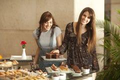 Duas mulheres novas que apreciam um bufete da sobremesa Imagens de Stock Royalty Free
