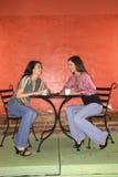 Duas mulheres novas que comem o café Imagens de Stock