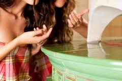 Duas mulheres novas que fazem a fragrância da erva do wellness fotos de stock royalty free