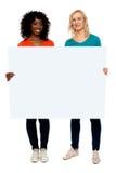 Duas mulheres novas que prendem o quadro de avisos em branco Fotografia de Stock Royalty Free