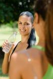 Duas mulheres novas que relaxam após a aptidão no parque Imagem de Stock