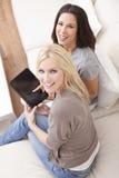 Duas mulheres novas que usam o computador da tabuleta em casa Fotografia de Stock