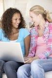 Duas mulheres novas que usam o computador portátil em casa Imagens de Stock Royalty Free