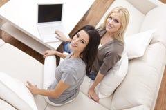 Duas mulheres novas que usam o computador portátil em casa Fotografia de Stock Royalty Free