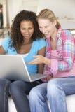 Duas mulheres novas que usam o computador portátil em casa Fotos de Stock