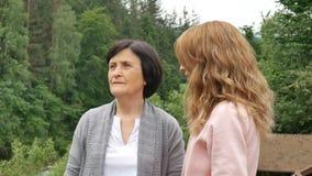 Duas mulheres, novo e idoso, estão olhando na distância e estão falando contra o contexto das montanhas e video estoque
