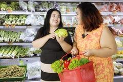 Duas mulheres obesos que compram vegetais orgânicos Fotografia de Stock