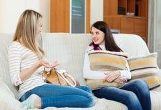 Duas mulheres ocasionais que bisbilhotam no sofá Imagem de Stock
