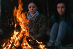 Duas mulheres olham o fogo em uma noite do verão Fim de semana do feriado da família imagem de stock