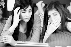 Duas mulheres preocuparam-se sobre más notícias na tabuleta fotos de stock